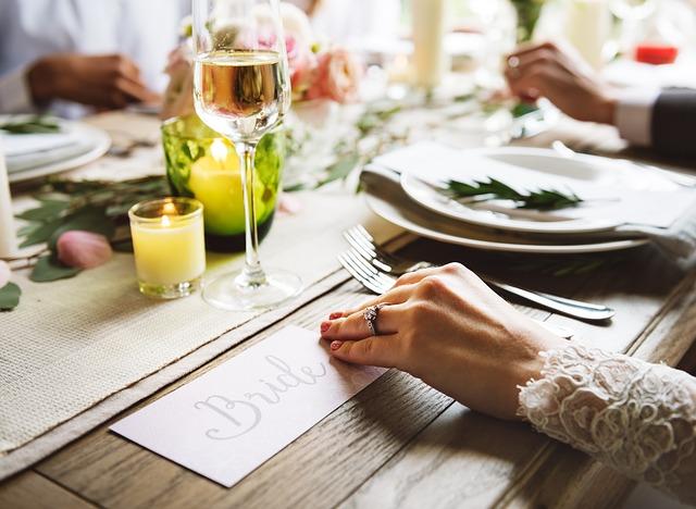"""Nevesta, ktorá v ruke drží menovku na stole s nápisom """"Bride"""""""