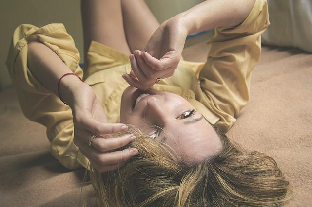 Usmiata žena v žltej blúzke a holými nohami leží na zemi.jpg