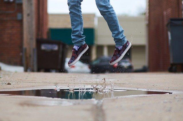 Človek v teniskách skáče do výšky nad mlákou.jpg