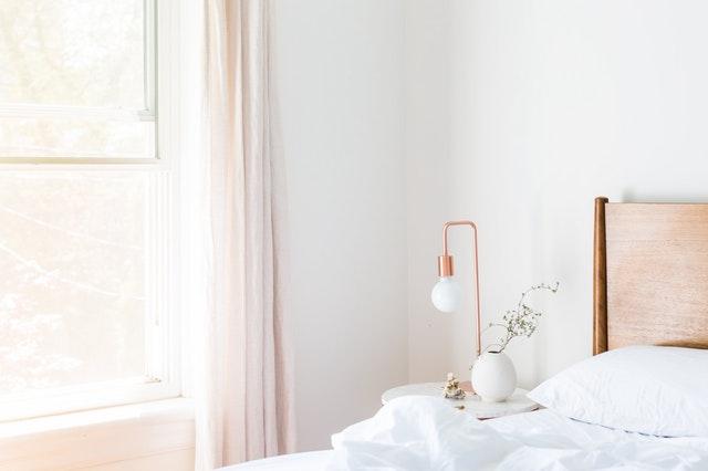 Posteľ pri okne a nočný stolík s lampou