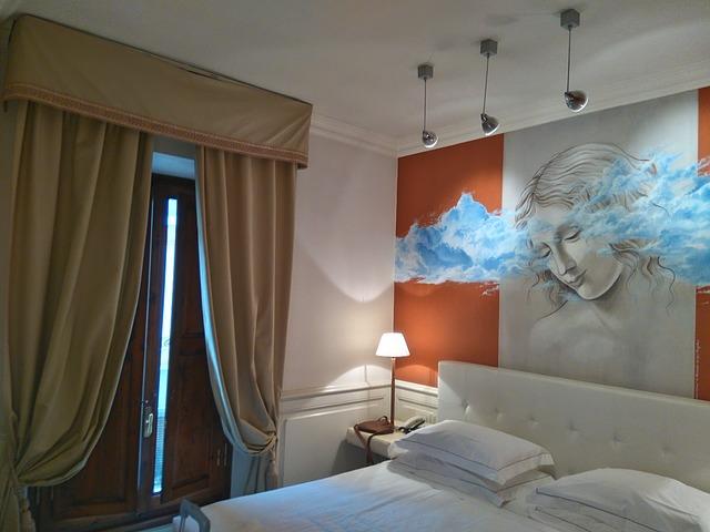 Spálňa s posteľou, nad ktorou je veľký obraz ženy